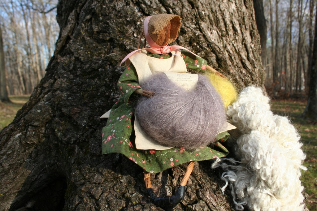 A handmade mountain folk figure with a walnut for a head sits with a cake of kid mohair blended with silk, a wound kid mohair/silk yarn ball in  a cream-ecru loopy mohair skein.