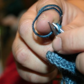 Knitter's hands with yarn and needle.