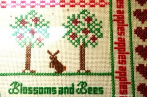 Counted-cross stitch rabbit in an apple-themed sampler.